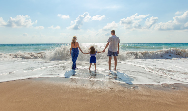 Famille sur la plage les pieds dans l'eau
