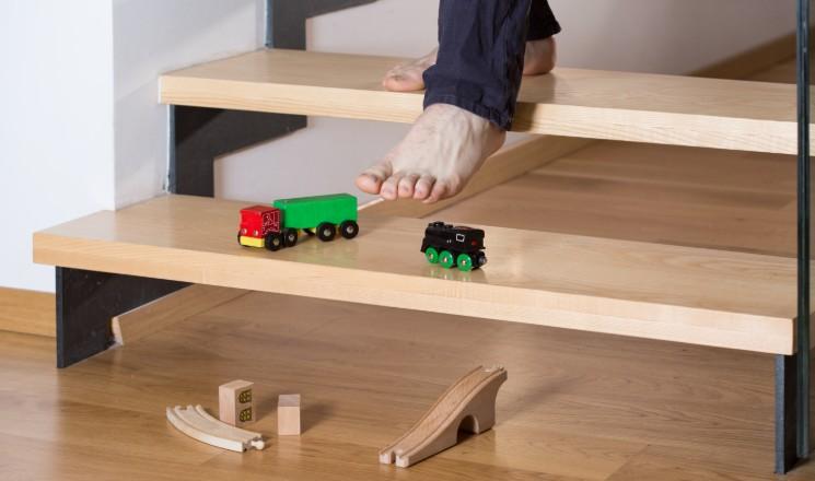 Personne qui s'apprête à glisser sur des jouets dans un escalier