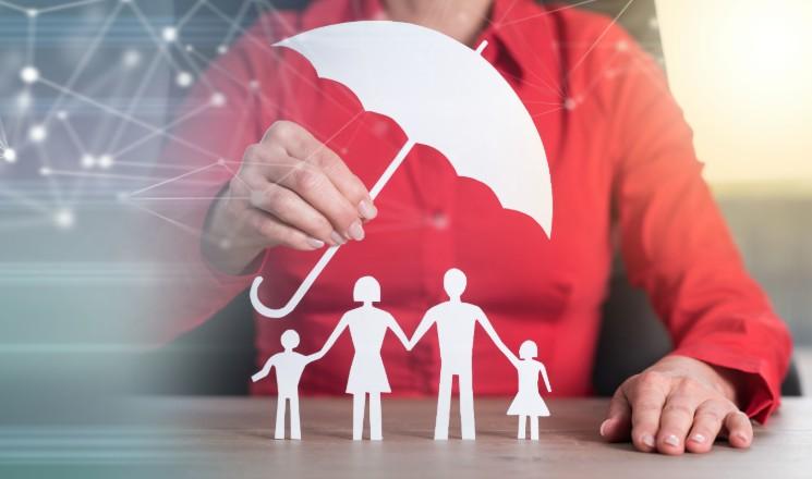 Femme qui protège des personnages en papier découpé avec un parapluie en papier