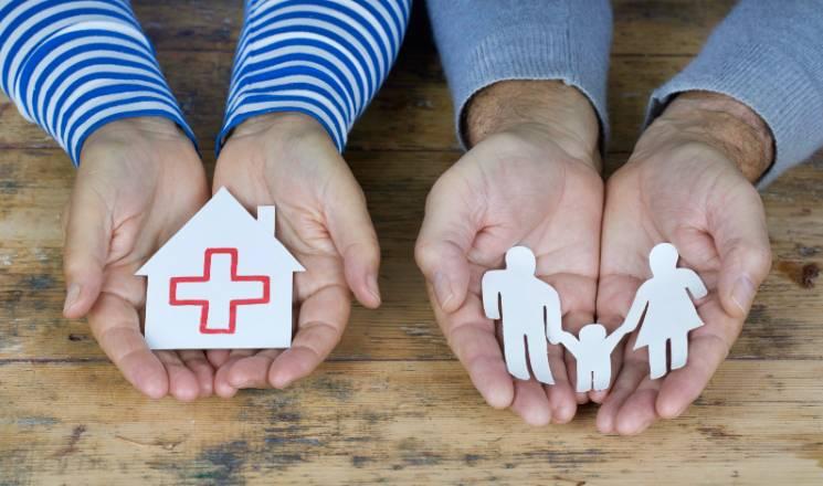 Une personne tient une maison en papier au creux de ses mains. Une autre personne tient des personnages en papier découpé au creux de ses mains.