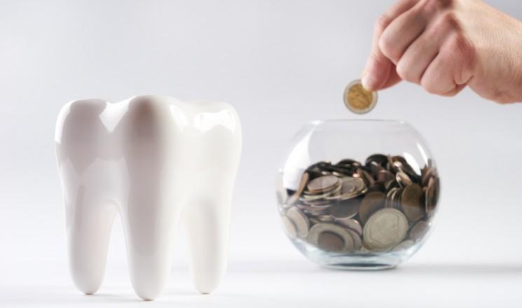 Sculpture de dent avec tirelire posée à côté