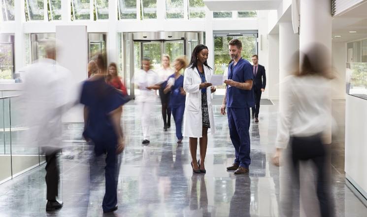 Contractuel hospitalier discutant avec une femme médecin dans le hall d'un hôpital