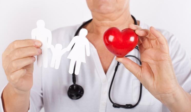 Médecin avec stéthoscope autour du cou tenant des personnages en papier découpé dans une main, et un coeur en bois rouge de l'autre main
