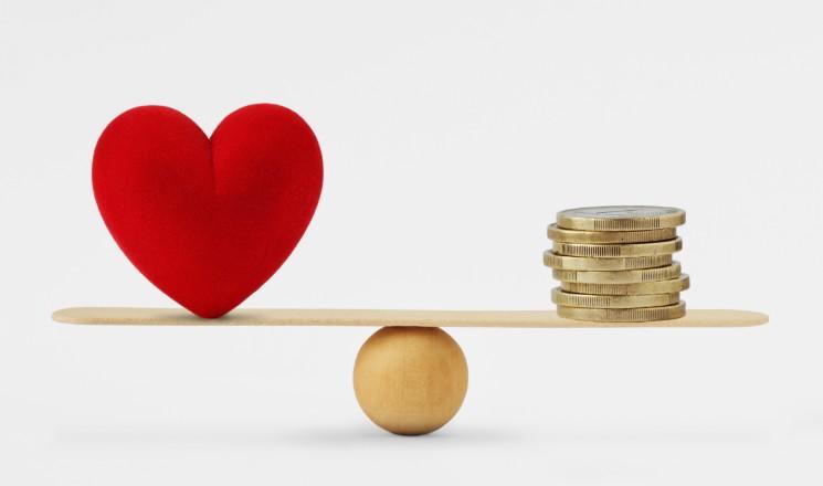 Balance avec coeur d'un côté et pile de pièces de monnaie de l'autre