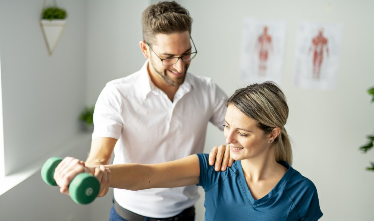 Séance de kiné : un praticien aide sa patiente à réaliser un exercice à l'aide d'une haltère