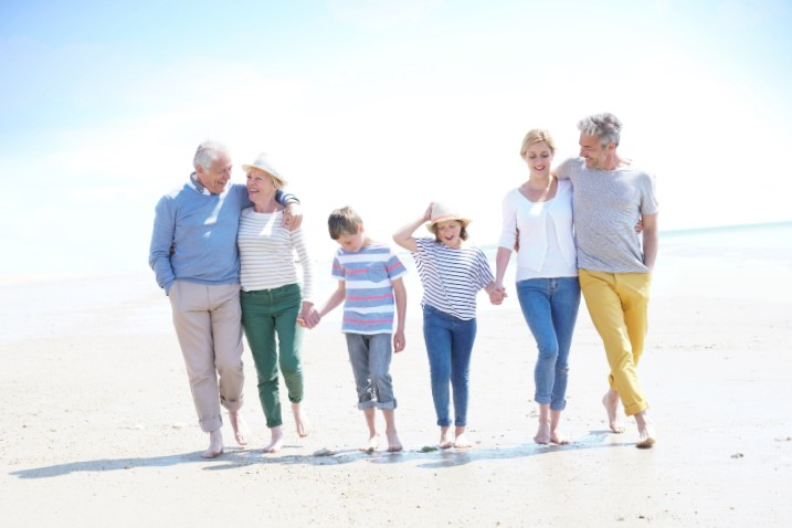 Grands parents, parents et petits enfants qui marchent sur une plage avec le sourire